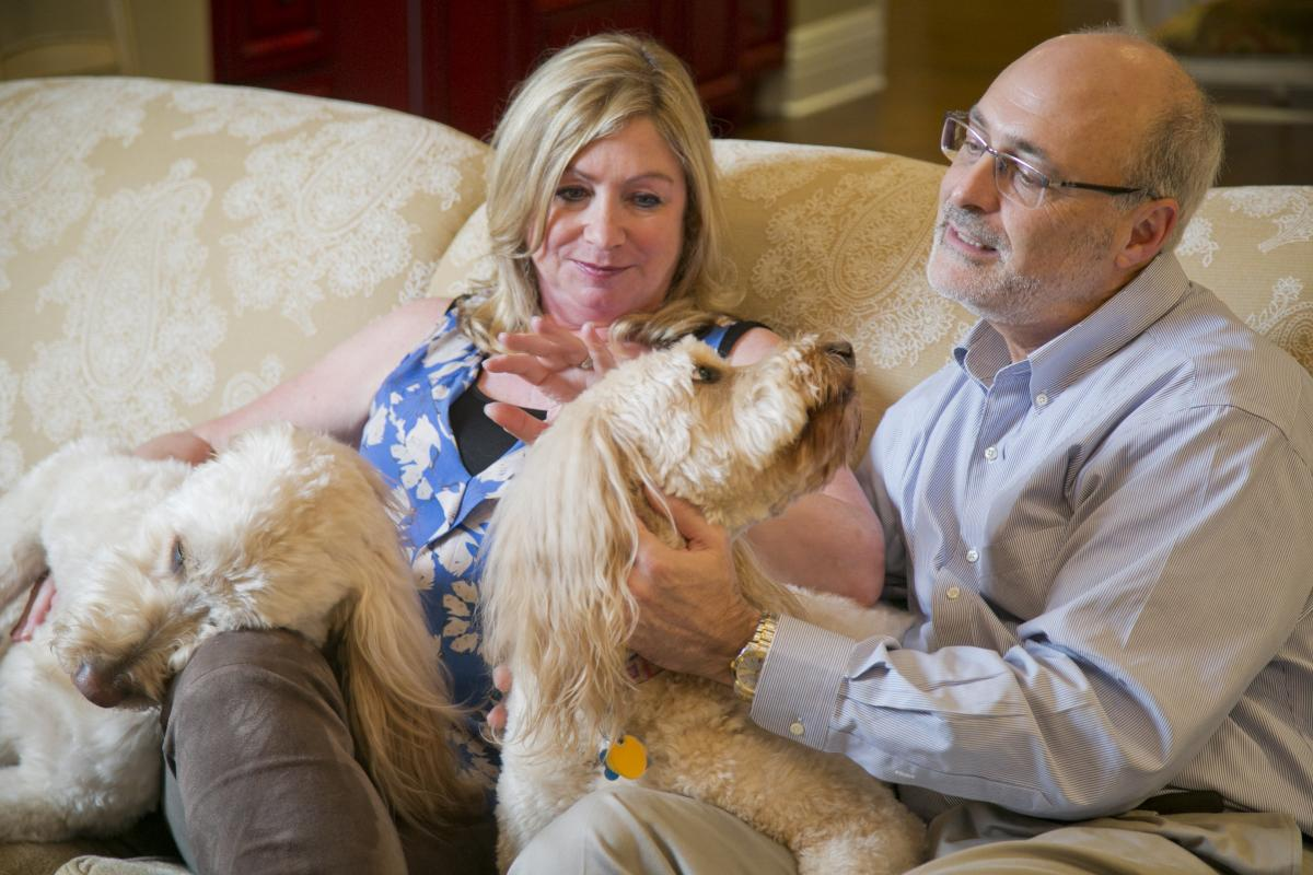 Michael Kastan, MD, PhD, executive director of the Duke Cancer Institute, and his wife, Kathy, relax at their Chapel Hill home with their dogs, Micah and Maggie. photo byJared Lazarus, Duke Photography