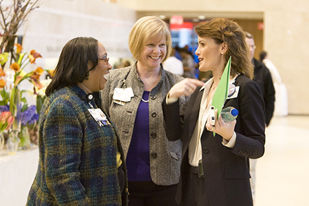 At the 2012 grand opening of Duke Cancer Center, Alison Andre, center, shares a moment of jubilation with then DCI administrator Carolyn Carpenter (right) and Deborah Page, Duke Human Resources.