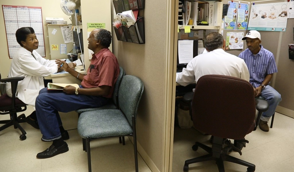 Two men receive screenings and health information in Durham's Lincoln Community Health Center during last year's MHI event.