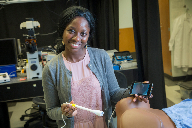 "Mercy Asiedu, a graduate student in Duke's Global Women's Health Technologies Center, shows the prototype speculum-free ""pocket colposcope"" that is currently being beta tested in several hospitals across the United States."