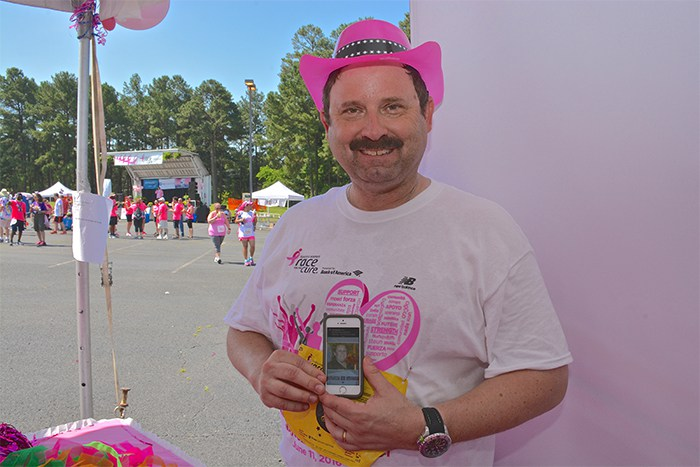 While participating in the 20th Annual Komen Triangle Race For The Cure on June 11, Joe Rasmus stops by to visit volunteers the Duke Cancer Institute tent. Here, he holds up a photo of his wife, Margaret, who lost her battle with cervical cancer on Valentine's Day.
