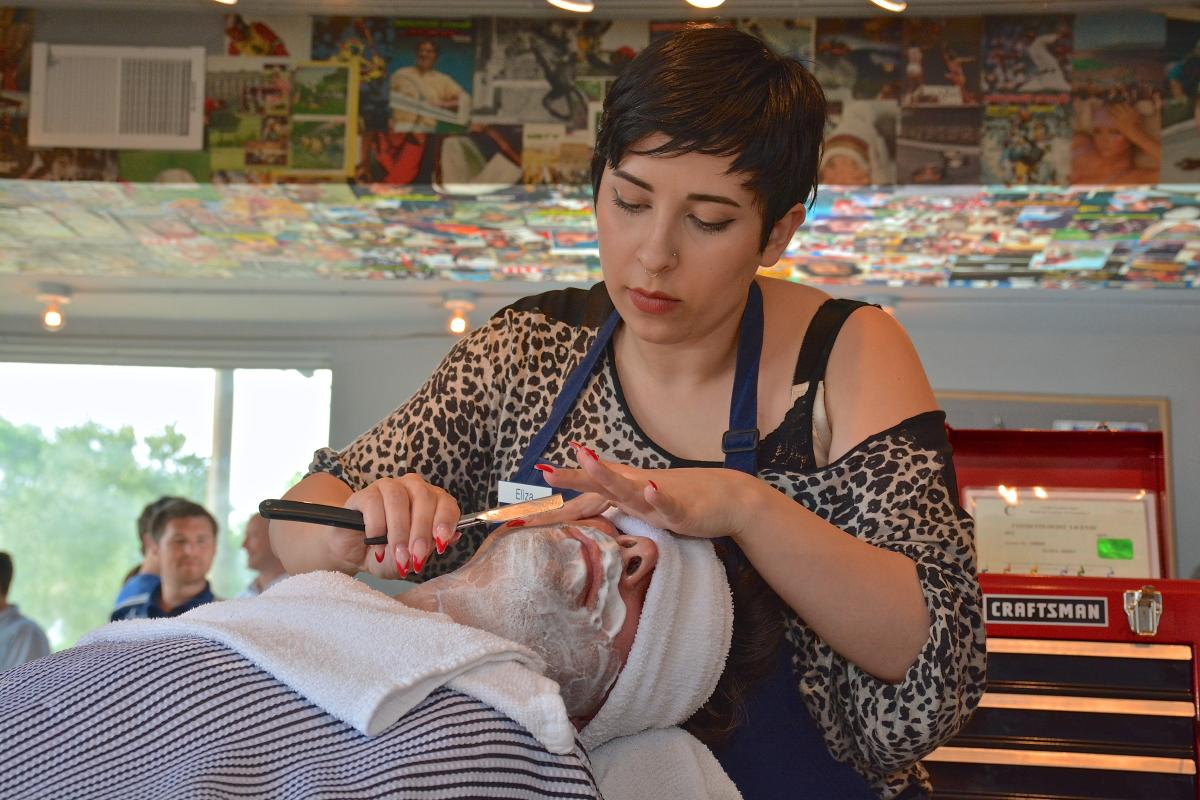 Eliza, one of the barbers at Pedro Williams, schools Dan George, MD, in an old fashioned hot shave.