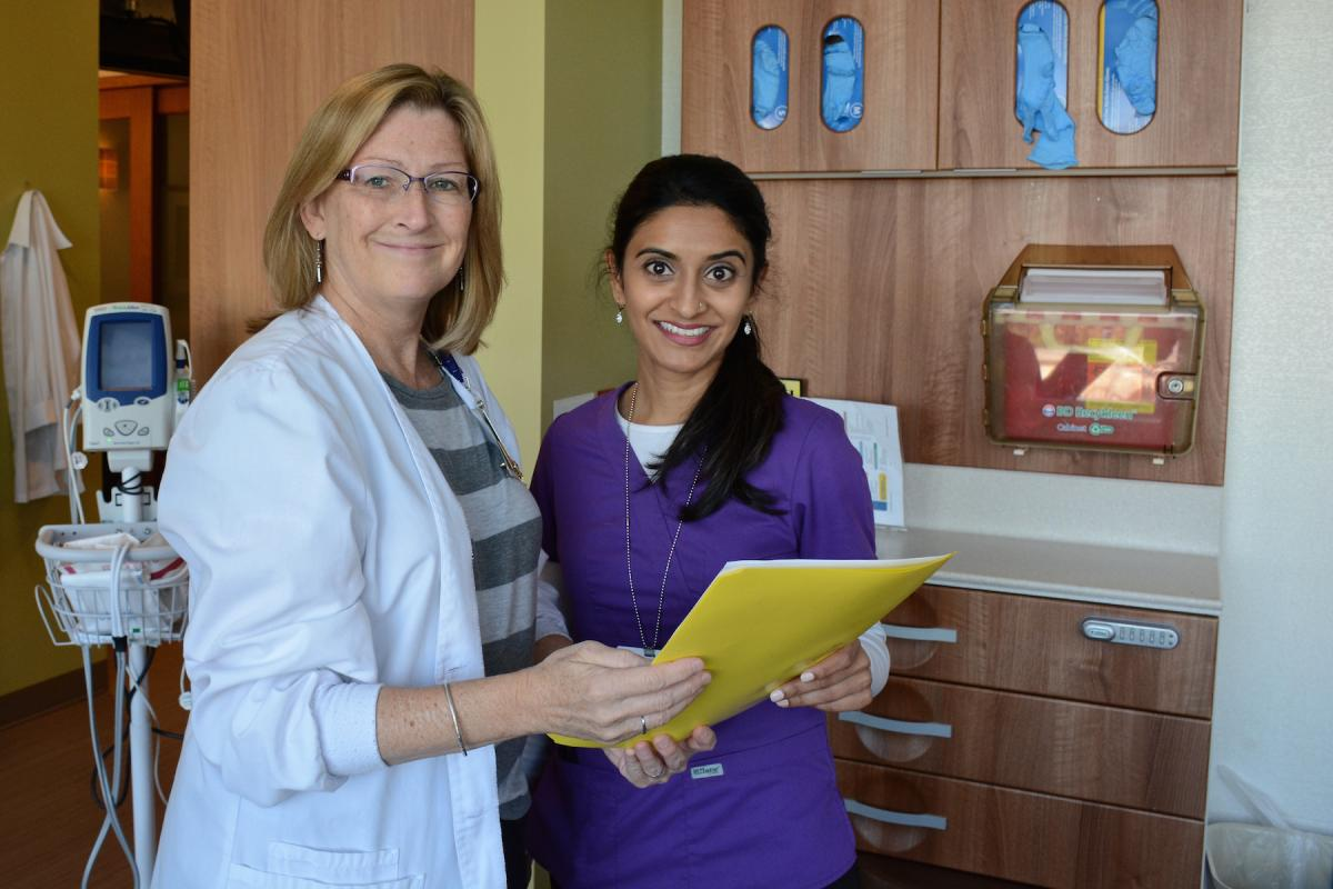 Ellen Parks, RN, OCN, reviews a patient chart with Hital Patel, RN, BSN, OCN, on Level 4 of the Duke Cancer Center.