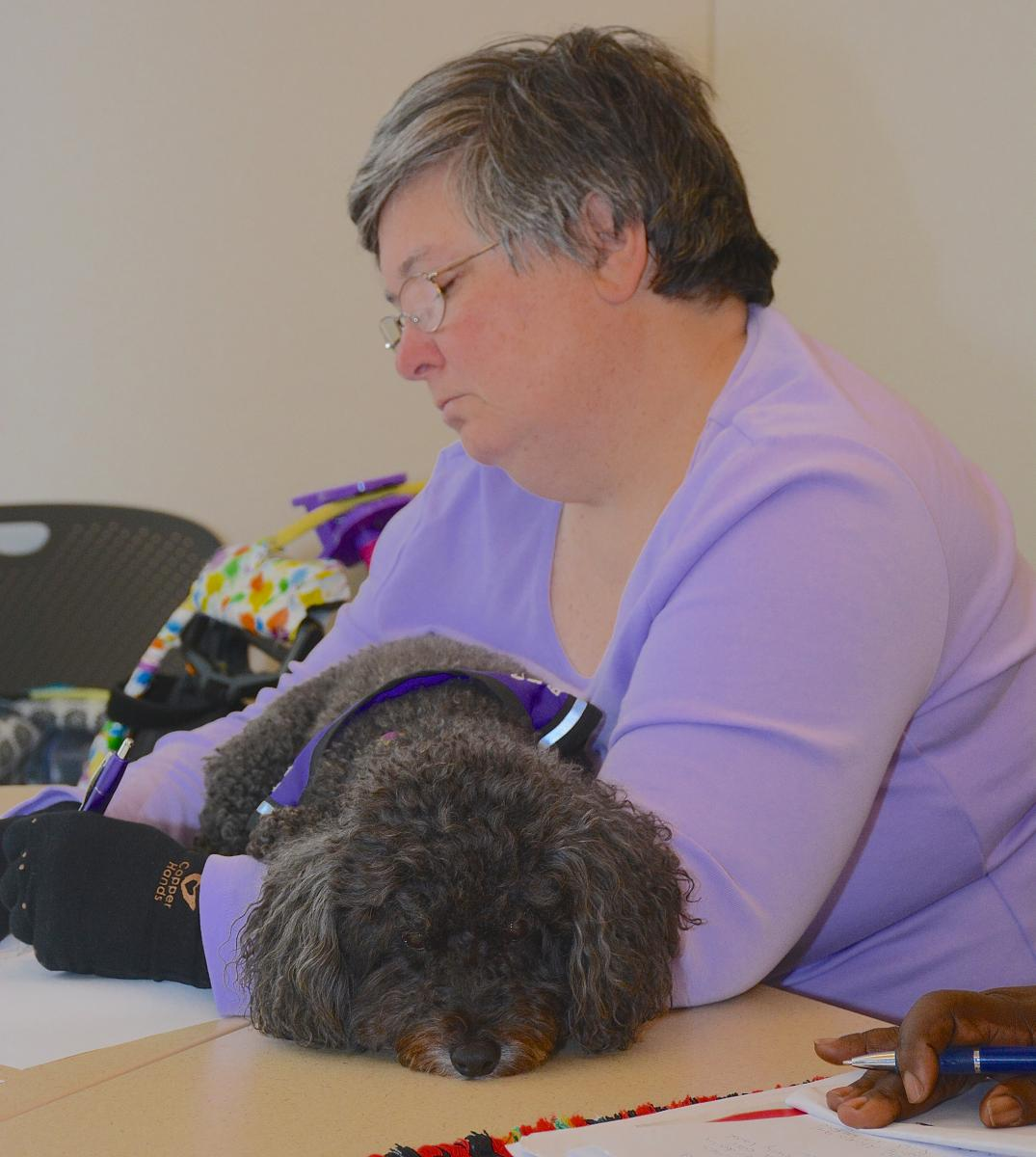 Peg Meerkatz, who battles progressive multiple sclerosis and diabetes, contributes a line to a poem started by breast cancer survivor Sheila Thompson. Her service dog, Esperanza, a bichon and poodle mix, relaxes in her arms as Meerkatz adds the finishing touch.