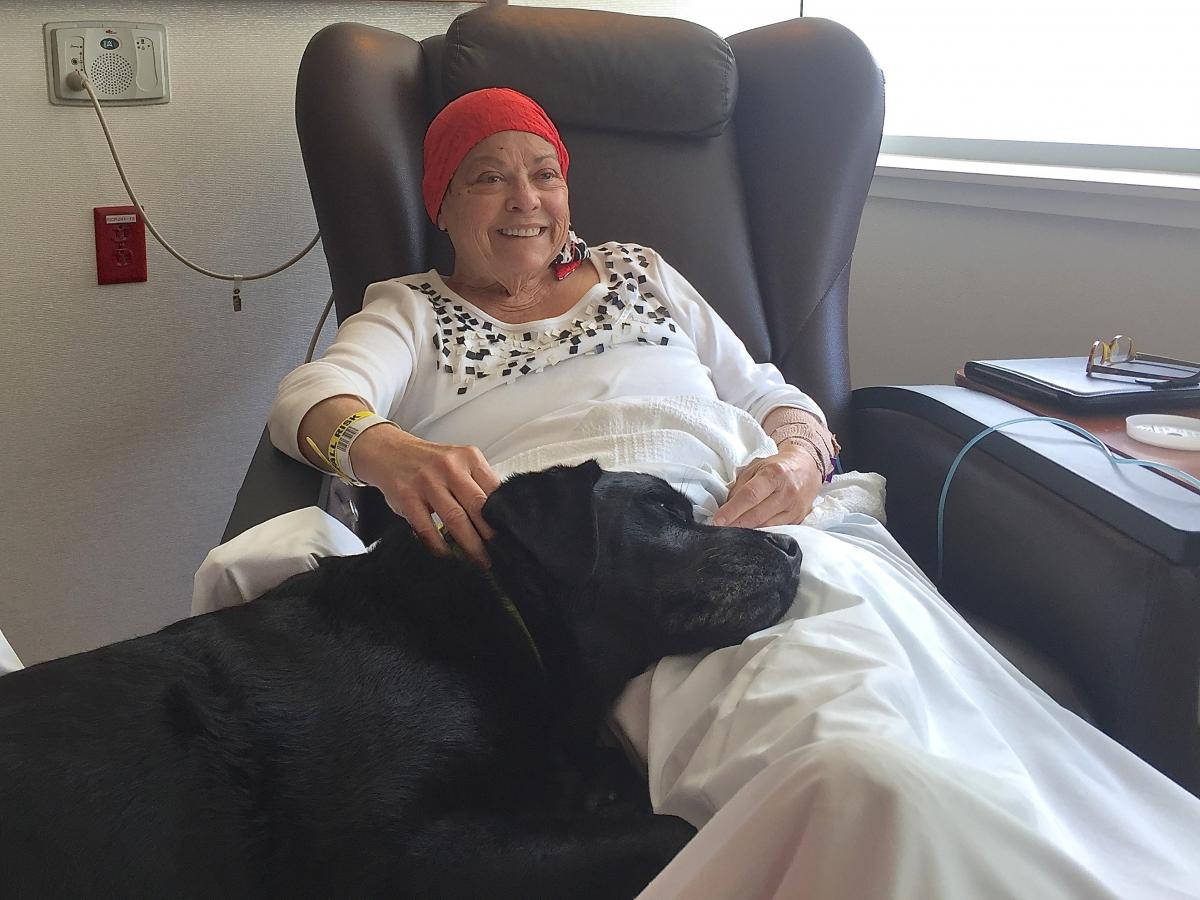 Sheila Evans enjoys the company of Kylie, a black Labrador retriever, while receiving chemotherapy at Duke Cancer Center. Kylie is a Pets At Duke therapy dog.