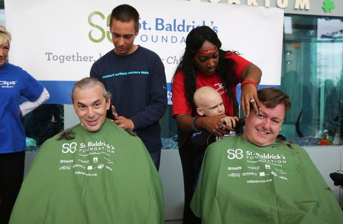 Doctors Dan Wechsler, left, and Waitman Aumann, get their heads shaved by their patients Jake May, left, and Douglas Hull.