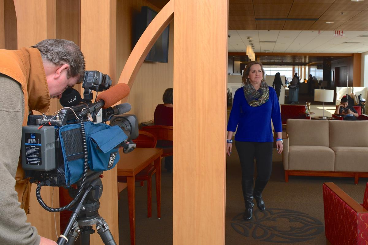 After interviewing with ABC 11's Caitlin Knute, Erin Wood strolls through the Duke Cancer Center as the station's photographer films her. Wood, an 8-year cancer survivor, and Team TushTush will be stepping out March 14 for the Second Annual CRUSH 5K and Fun Walk.