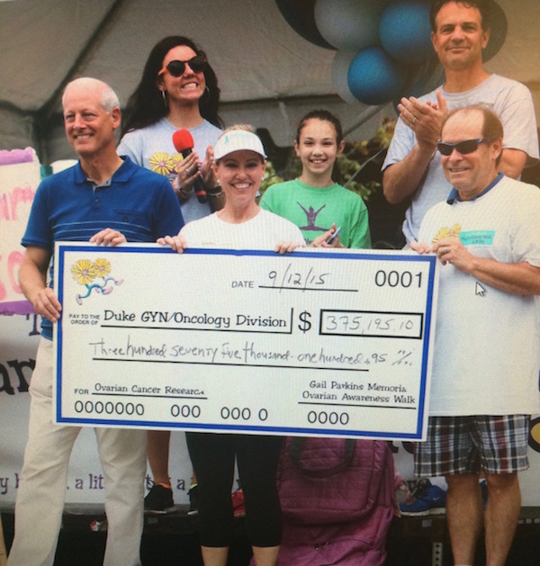 Melanie Bacheler presents a check made out to the Duke GYN/Oncology division to Andrew Berchuck, MD (at left) and Fidel Valea, MD (at right) at last year's Gail Parkins Memorial Ovarian Cancer Walk and 5K Run. Bacheler's husband Tim and her daughters — all active volunteers for the cause, are behind them. This year's event is being held this Saturday, September 17.
