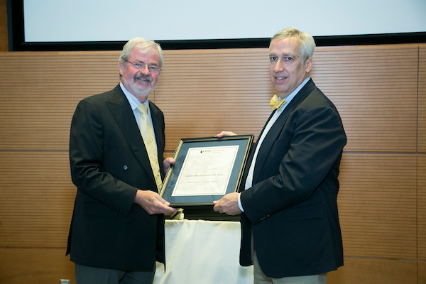 Edward Buckley, MD,Chair of the Department of Ophthalmology and Vice Dean for Education, School of Medicine, presents a Master Clinician/Teacher Award to Carlos de Castro, III, MD. (at right)
