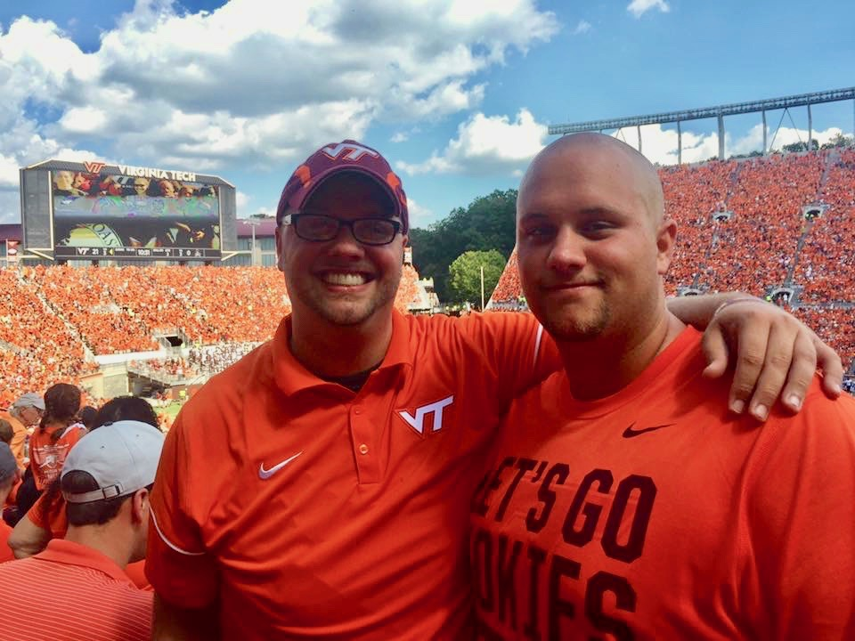 Blacksburg, Virginia resident Anthony Willard, a financial analyst for Wells Fargo, developed bladder cancer six years ago at the age of 24. An avid sports fan, his favorite teams are the Duke Blue Devils (basketball) and Virginia Tech Hokies (football). Here he is (at left) with his brother Jake enjoying a Hokies game on September 24, 2016.