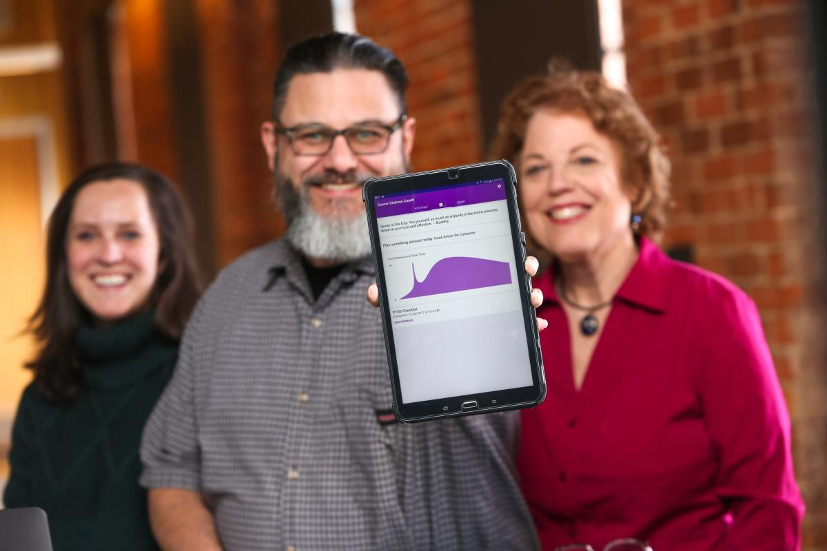 Medical student Callie Berkowitz, lead Android developer Mike Revoir, and project investigator Sophia Smith show off the Cancer Distress Coach app.