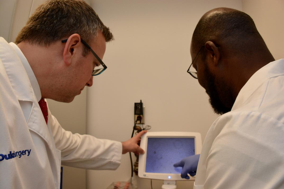 Urologic oncologist Brant Inman, MD, MS, and research technician Wiguins Etienne analyze bladder cancer cell lines at Inman's Urologic Oncology Laboratory. The lab is taking normal bladder cells and exposing them to a large number of potential carcinogens.