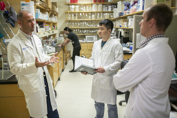Peter Fecci, MD, PhD, talks with members of his lab
