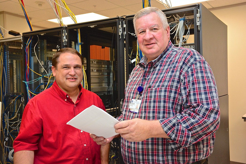 Chad McLamb, Web Services Administrator, and Tim Steele, Clinical Research Manager, review settings in the computer room, which houses all the server compute and storage used by users and departments throughout the DCI. The server environment is comprised of both physical stand-alone servers and an environment of virtual servers. The room is environmentally controlled with multiple layers of access control to ensure the data is physically secure. All data within the room is routinely backed up and stored offsite for disaster recovery and help ensure business continuity.