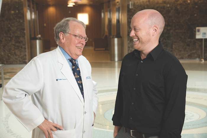 Joseph Moore, MD, (left) treated researcher Kris Wood for non-Hodgkin's lymphoma.