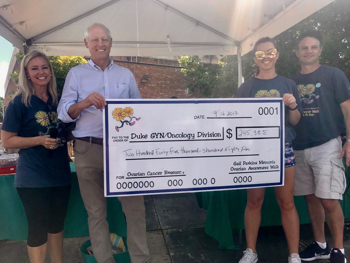 Gynecologic oncologist Andrew Berchuck, MD (center) receives a check, representing the proceeds of the Gail Parkins Memorial Ovarian Cancer Walk and 5K run, from event organizer Melanie Bacheler (left), her husband Tim (right) and Bacheler's niece.