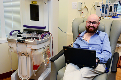 "Even while undergoing specialized treatment (photopheresis) for a bone marrow transplant complication, clinical trial coordinator Matt Williamson, RN, BSN, — with Duke's Adult Blood & Marrow Transplant Program — is hard at work at his laptop. ""To have the chance to help fight the fight against disease is such an amazing opportunity and I'm extremely grateful to be a part of that fight here at Duke,"" he said."